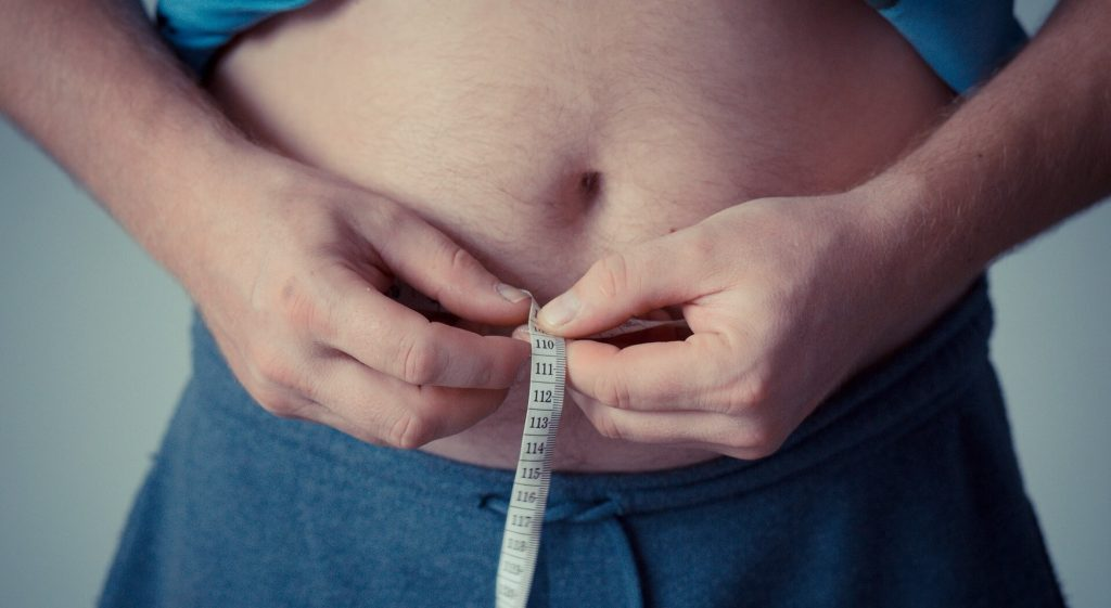 Overweight male measuring waist circumference