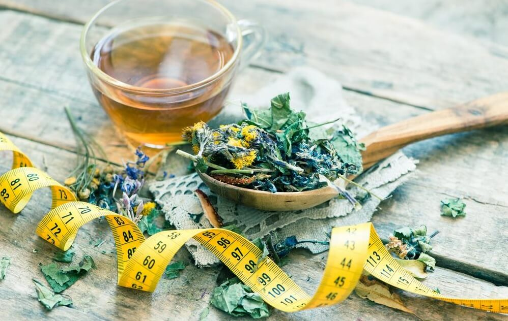 Detox tea leaves alongside cup of brewed tea