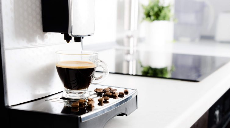White home espresso machine with cup and coffee beans