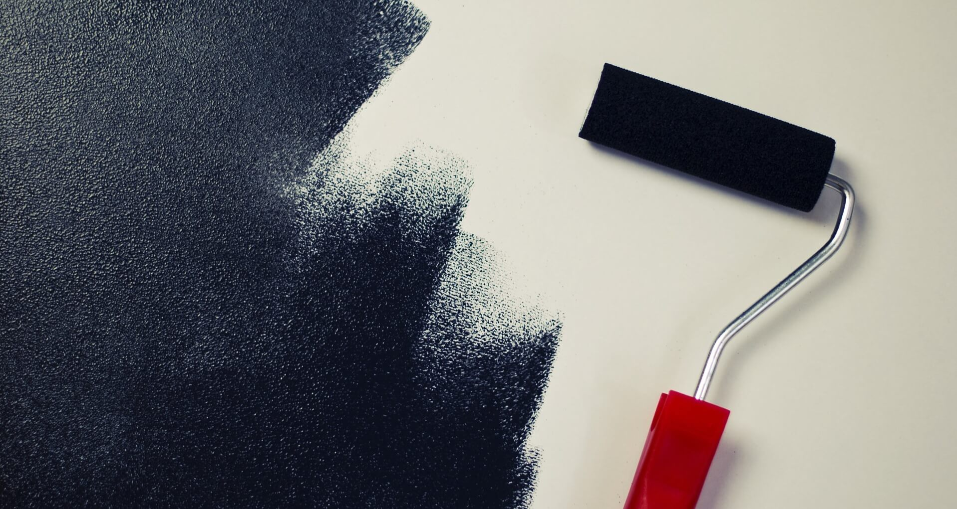Black paint roller on white wall